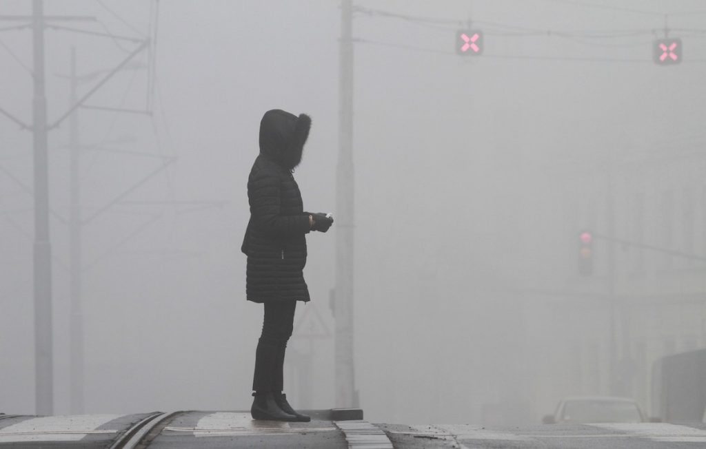 A commuter waits to cross a street as air pollution blocks the sky over Belgrade in Serbia in 2020. Photo: AFP/Milos Miskov/Anadolu Agency